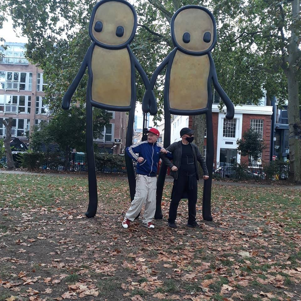 Unseen Tour Guide Pete and street artist Stik pose in front of his new art in Hackney
